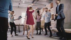 Lycklig Caucasian kvinnaledaredans på det tillfälliga kontorspartiet Det multietniska affärsfolket firar framgångultrarapid stock video
