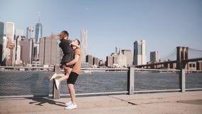 Lycklig Caucasian man som möter hans flickvän, kramar och ler på solig Manhattan horisont i New York City ultrarapid lager videofilmer