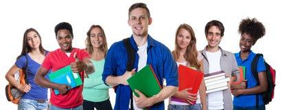 Lycklig caucasian manlig student med gruppen av internationella studenter royaltyfria foton