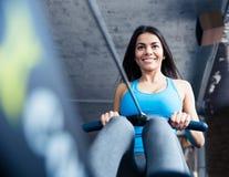Lycklig charmig kvinna som utarbetar på idrottshallen Royaltyfri Foto