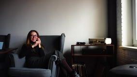 Lycklig charmig student för ung dam som talar på telefonen och, att posera och att le som in sitter i stol i stilfullt kafé arkivfilmer
