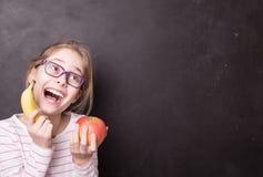Lycklig chidflicka med äpplet och bananen på den svart tavlan arkivbilder