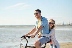 Lycklig cykel för barnparridning på stranden arkivfoton