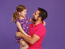 Lycklig dag för fader` s! gullig farsa och dotter som kramar på violetbaksida Royaltyfri Bild
