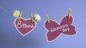 Lycklig dag för kvinna` s Dag för kvinna` s på rosa färgpapper som hänger på ett rep nära en rosa hjärta som dekoreras med blommo stock video