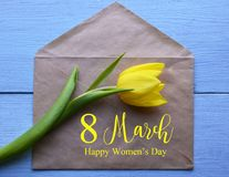 Lycklig dag för kvinna` s Gult tulpan- och papperskuvert med text på blå träbakgrund Royaltyfri Bild
