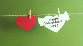 Lycklig dag för kvinna` s Händer som fixar en vitbokhjärta med vingar på en kabel med en klädnypa på grön bakgrund stock video