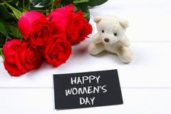 Lycklig dag för kvinna` s Mars 8 Rosor, nallebjörn och svart tavla på en vit trätabell Royaltyfri Foto