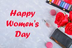 Lycklig dag för kvinna` s Mars 8 Rosor, skönhetsmedel, makron och en handväska på grånar konkret bakgrund Royaltyfria Foton