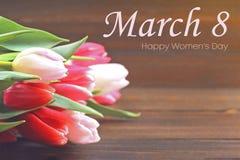 Lycklig dag för kvinna` s Mars 8 Tulpan på en brun trätabell Fotografering för Bildbyråer