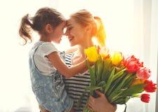 Lycklig dag för moder` s! barndottern ger modern en bukett av f royaltyfria foton