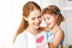 Lycklig dag för moder` s! Barndottern gratulerar mammor och ger sig Fotografering för Bildbyråer