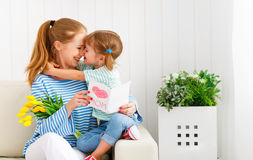 Lycklig dag för moder` s! Barndottern gratulerar mammor och ger sig arkivbilder