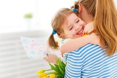 Lycklig dag för moder` s! Barndottern gratulerar mammor och ger sig Arkivfoto