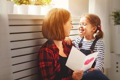 Lycklig dag för moder` s! Dottern ger hennes moder en vykort Royaltyfri Foto