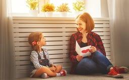 Lycklig dag för moder` s! Dottern ger hennes moder en vykort Arkivbilder