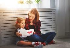 Lycklig dag för moder` s! Dottern ger hennes moder en vykort Arkivfoto