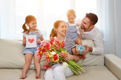 Lycklig dag för moder` s! fadern och barn gratulerar modern på H arkivbild