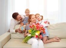 Lycklig dag för moder` s! fadern och barn gratulerar modern på H fotografering för bildbyråer