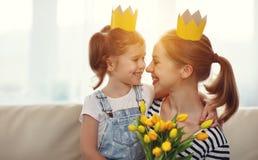 Lycklig dag för moder` s! moder- och barndotter i kronor och med arkivbild