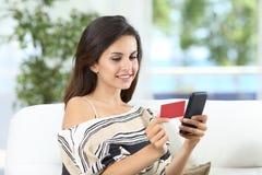 Lycklig dam som betalar direktanslutet genom att använda en kreditkort hemma arkivbild