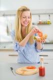 Lycklig danandesmörgås för ung kvinna i kök Royaltyfri Foto