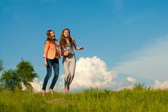 Lycklig dans för två härliga unga kvinnor & blå sky Arkivbild