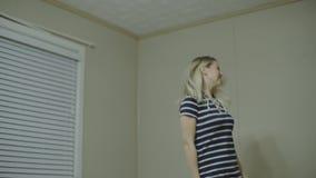 Lycklig dans för ung kvinna i bärande pyjamas för kök i morgonen som hemma lyssnar till musik på smartphonen och kaffe stock video
