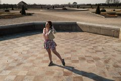 Lycklig dans för ung kvinna i en tom springbrunn som bär en färgrik kjol arkivbilder