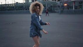 Lycklig dansa flicka på gatan Gå på gatan, moderiktig ung kvinna med frodigt hår lager videofilmer