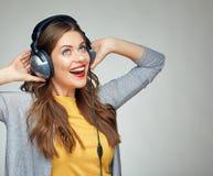 Lycklig danskvinna med hörlurar som isoleras på grå bakgrund Royaltyfria Bilder