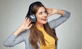 Lycklig danskvinna med hörlurar som isoleras på grå bakgrund Royaltyfria Foton