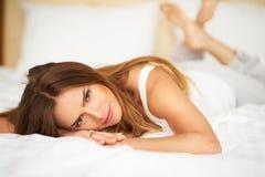 Lycklig delikat kvinna som ligger på säng med korsade ben som ser in i kamera i sovrum Royaltyfria Foton