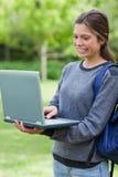 Lycklig deltagare som ser avskärma av henne bärbar dator Royaltyfri Foto