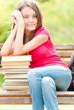 Lycklig deltagareflicka på bänk med stapeln av böcker Arkivfoton