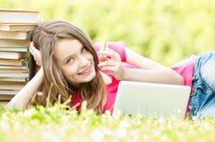 Lycklig deltagareflicka som ligger på gräs med bärbar dator arkivbild