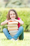 Lycklig deltagareflicka som sitter nära stapel av böcker Arkivfoto