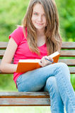 Lycklig deltagareflicka som sitter på bänk med boken Royaltyfri Foto