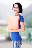 Lycklig deltagarekvinna med anteckningsböcker Arkivbild