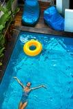 lycklig din feriesommar för familj Kvinna som tycker om semestern som svävar i simbassäng Royaltyfria Bilder