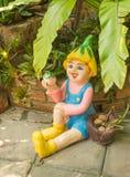 Lycklig docka i en trädgård Royaltyfri Fotografi
