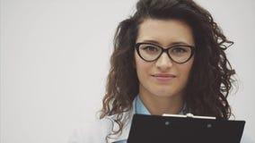 Lycklig doktor för ung kvinna Under detta rymmer en svart mapp med dokument, har ett vänligt uttryck Gå att se lager videofilmer