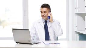 Lycklig doktor med bärbara datorn som kallar på smartphonen lager videofilmer