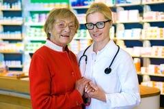 Lycklig doktor med den kvinnliga patienten i apotek Royaltyfria Foton