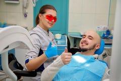 Lycklig doktor och patient i tand- le för kontor Arkivfoton