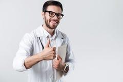 Lycklig doktor som sätter upp hans stora finger Arkivfoto