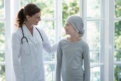 Lycklig doktor som stöttar det positiva barnet med den bärande sjaletten för cancer royaltyfri fotografi