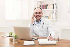 Lycklig doktor som talar på telefonen med hans patient royaltyfri fotografi
