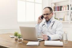 Lycklig doktor som talar på telefonen med hans patient arkivfoto