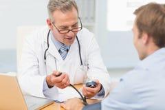 Lycklig doktor som tar hans patienter blodtryck Royaltyfri Bild